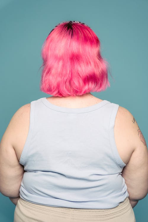 Back view of young plus size female in tank top with pink dyed hair standing against blue background