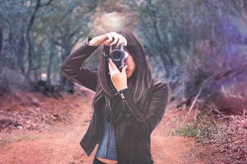 Woman Wearing Black Leather Jacket Holding Camera
