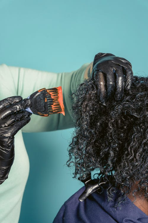 Hairstylist dying hair of black client
