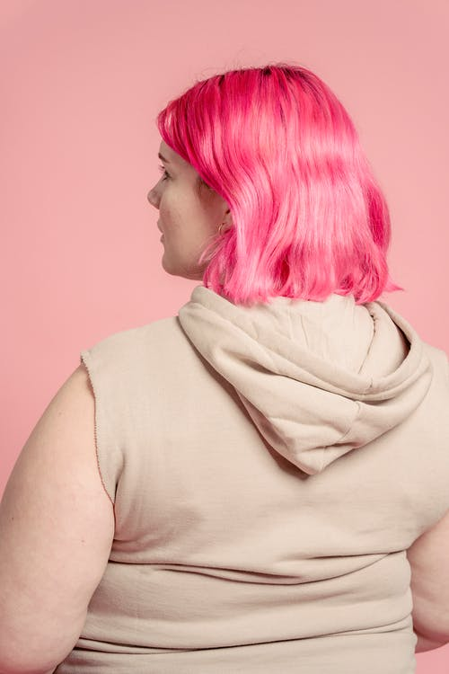 Serious young obese woman with colorful hair