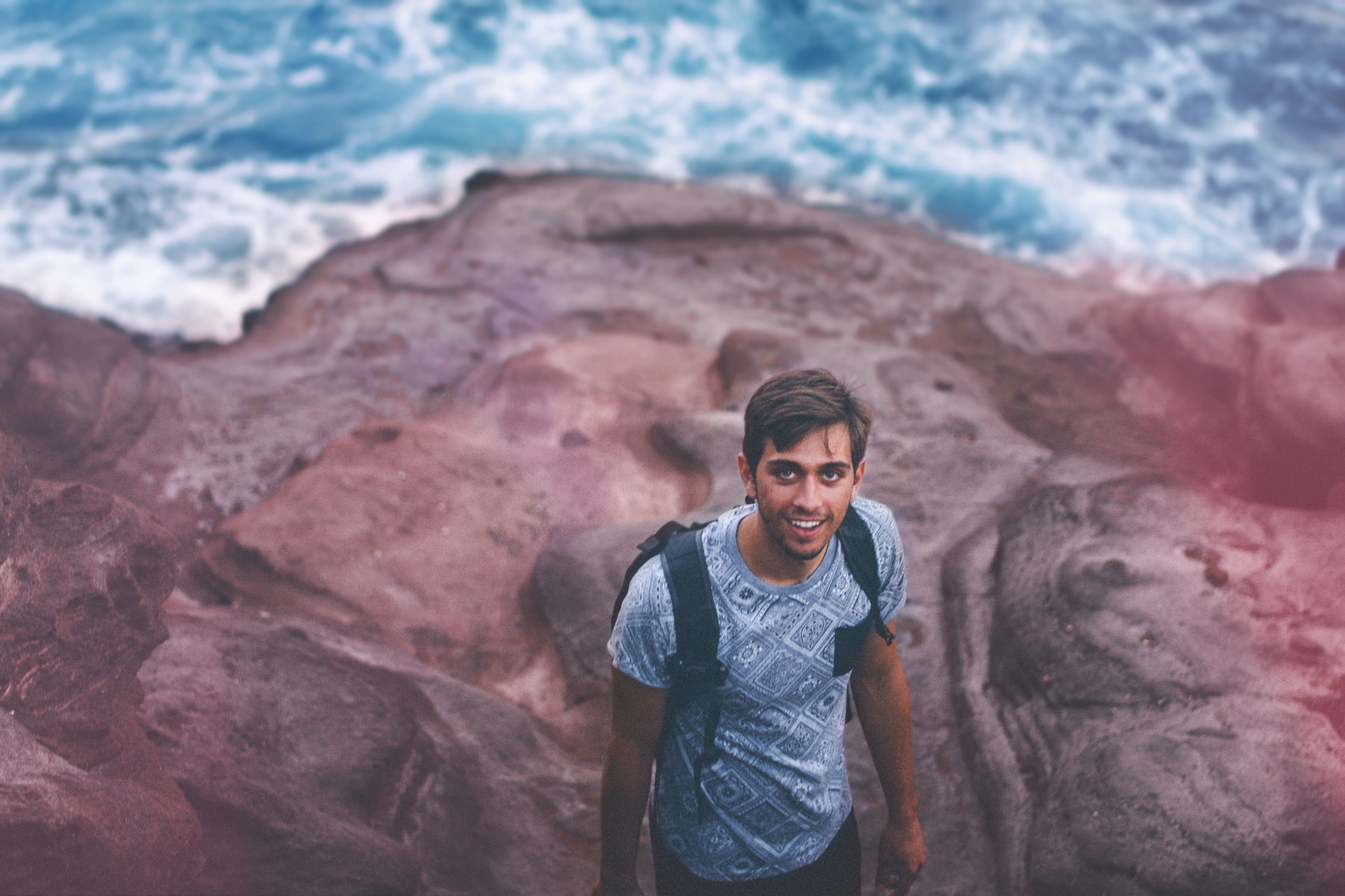 Photo Of Man Wearing Blue Shirt And Backpack Near Ocean