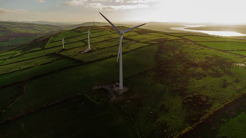 White Wind Turbine on Green Grass Field
