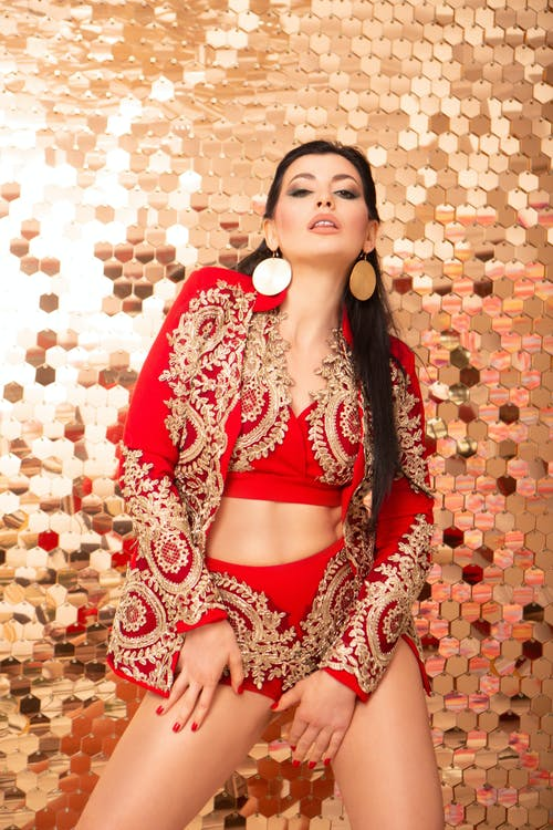 Charming female in stylish red clothes with bright makeup and accessories posing near glowing wall and looking at camera