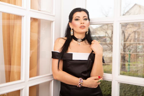 Gorgeous female in elegant black outfit with lewelry and bright makeup standing near window while looking at camera