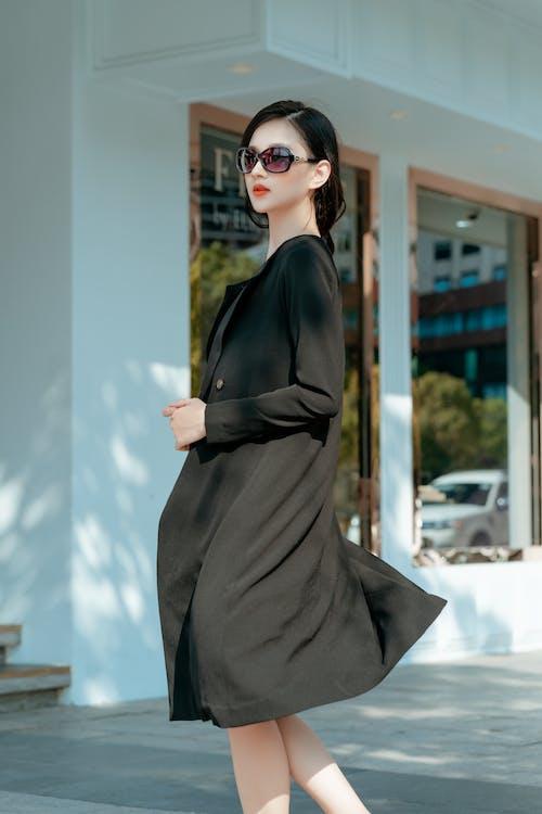 Woman in Black Long Sleeve Dress Wearing Black Sunglasses