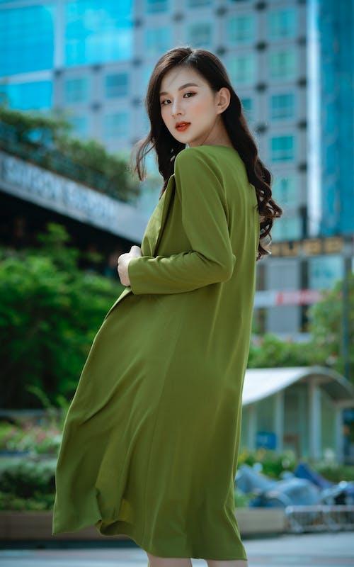 Woman in Yellow Long Sleeve Dress Standing Near Green Trees