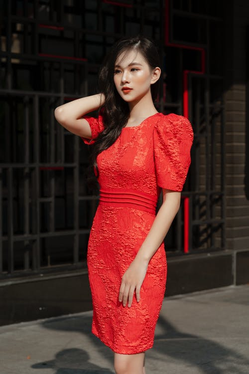 Woman in Red Floral Dress Standing on Sidewalk
