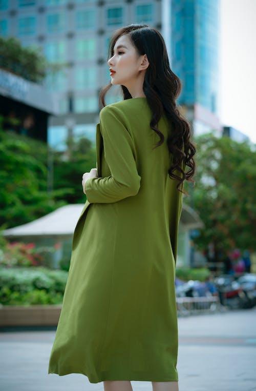 Woman in Yellow Coat Standing Near Green Plants