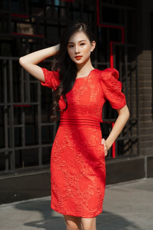 Woman in Red Floral Dress Standing on Black Asphalt Road