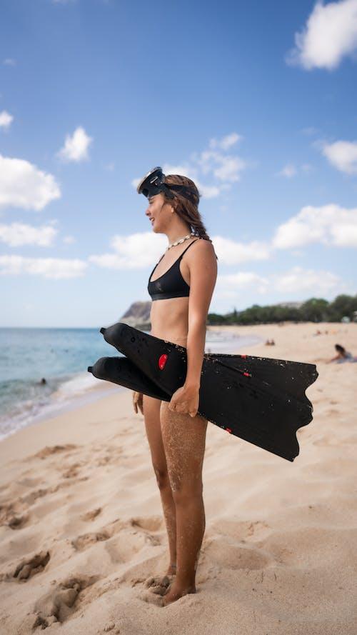 Woman in Black and White Bikini Holding Black Surfboard Standing on Beach