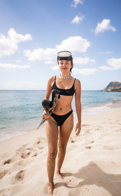 Full body of cheerful young woman in black swimwear standing with flippers in hand on sandy coast against blue ocean in sunny day