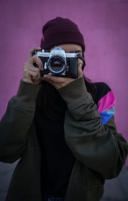 Person in Black Jacket Holding Silver and Black Camera