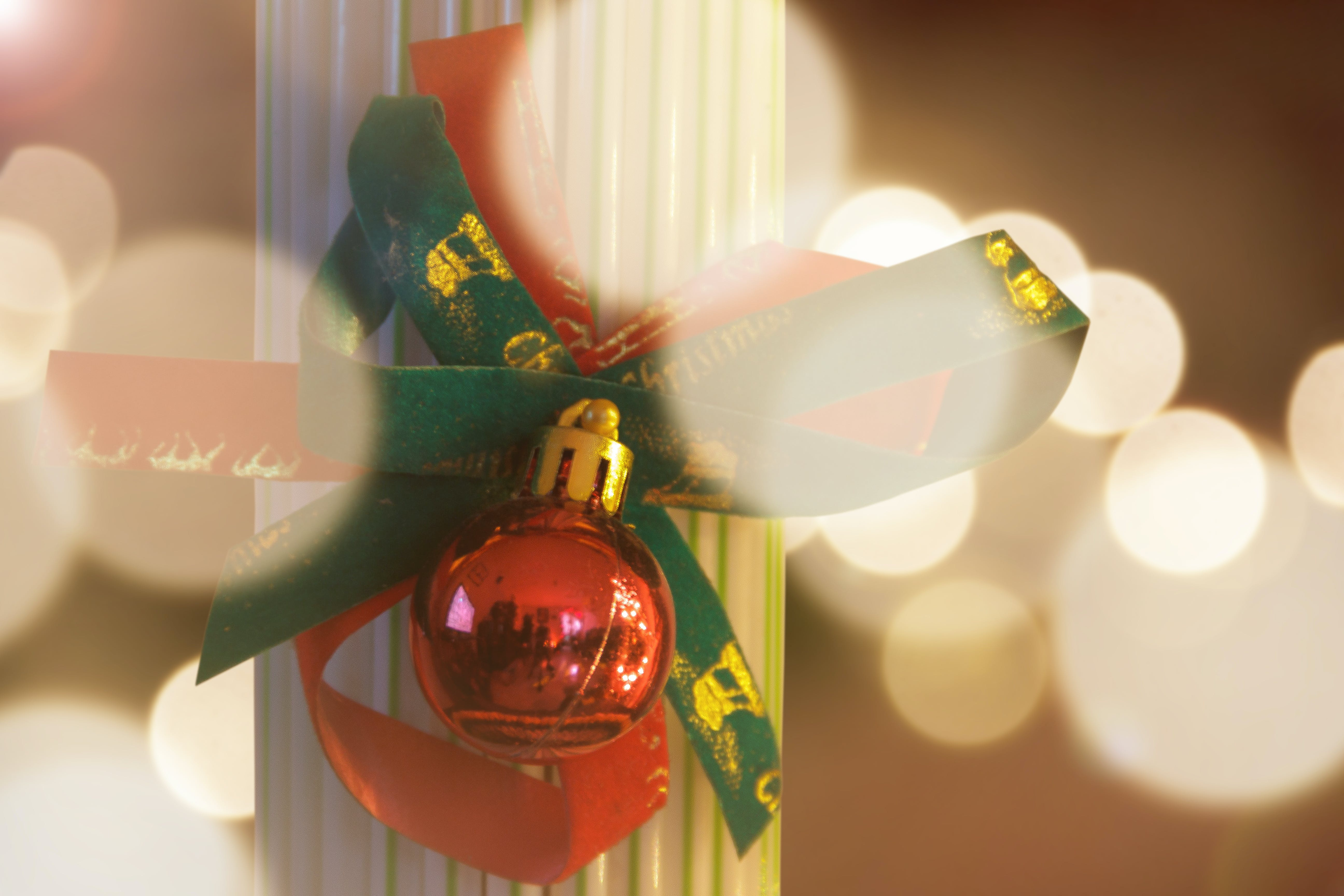 Photography Of Red Bauble With Green Ribbon