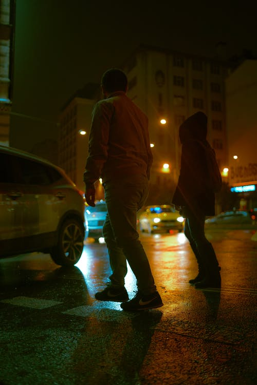 Full body of unrecognizable couple crossing asphalt road with glowing vehicles and buildings at night in town district