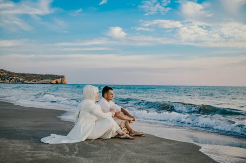 Man and Woman in White Dress Sitting on Beach