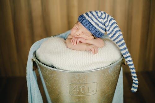 Adorable baby in nightcap sleeping in bucket