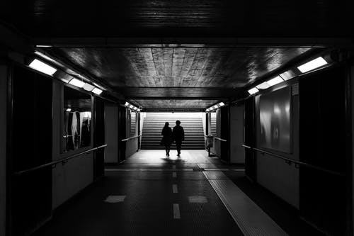 Back view black and white of unrecognizable passengers walking to stairs in subway station