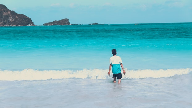 Photo of Man Walking by the Seashore