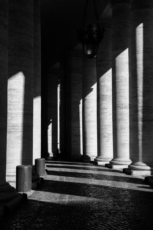 Black and white of aged stone building with columns and cobbled floor in linear shadows