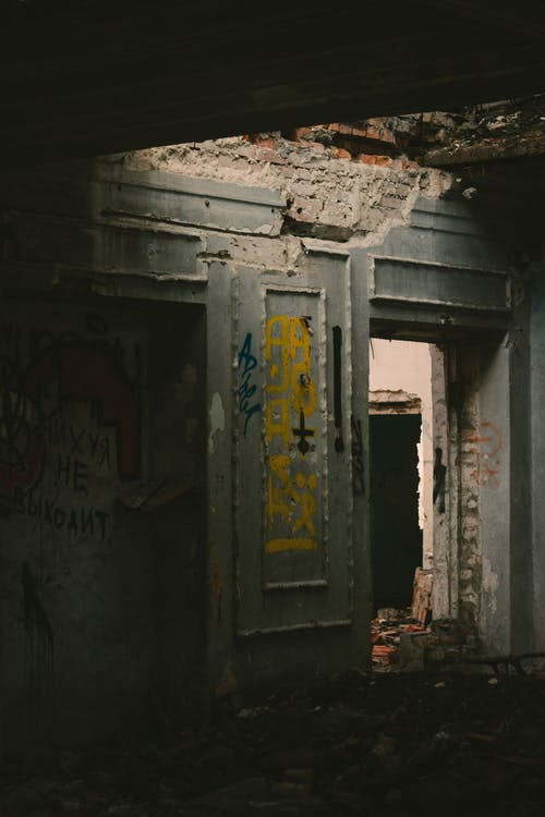 Dark room with grungy graffiti on damaged walls and shabby doorway inside desolate brick building