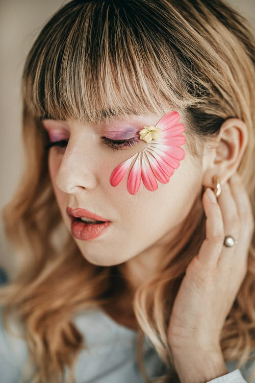 Crop tender woman with makeup and blooming flower petals with pleasant aroma on face looking down