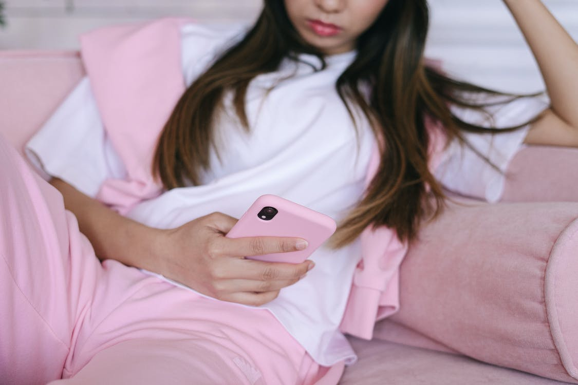 Woman in White Shirt Holding Iphone