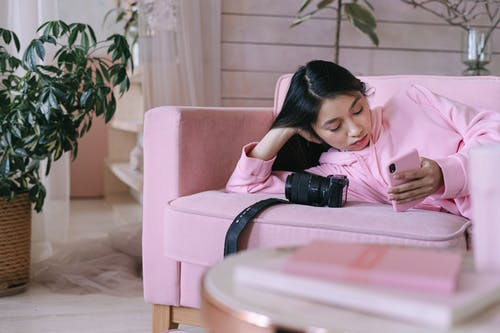 Girl in Pink Long Sleeve Shirt Sitting on White Chair