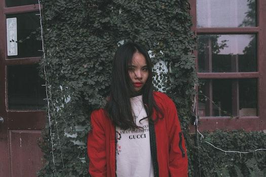 Photo of Woman Standing Near Window Wearing Red Jacket