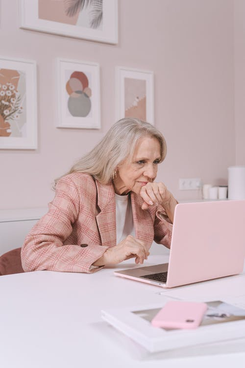 Woman in Pink Sweater Sitting on Bed