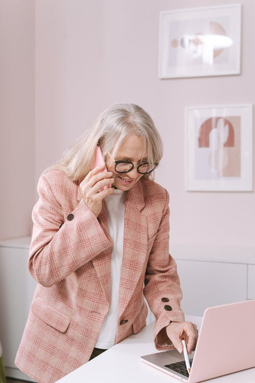 An Elderly Woman in a Pink Plaid Suit Using Her Phone While Holding a Pen to a Laptop
