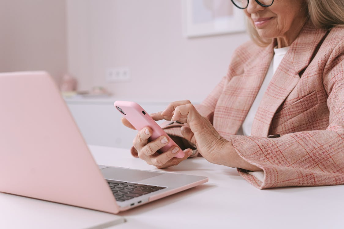 An Elderly Woman in Pink Plaid Suit Using a Smartphone in Front of a Laptop