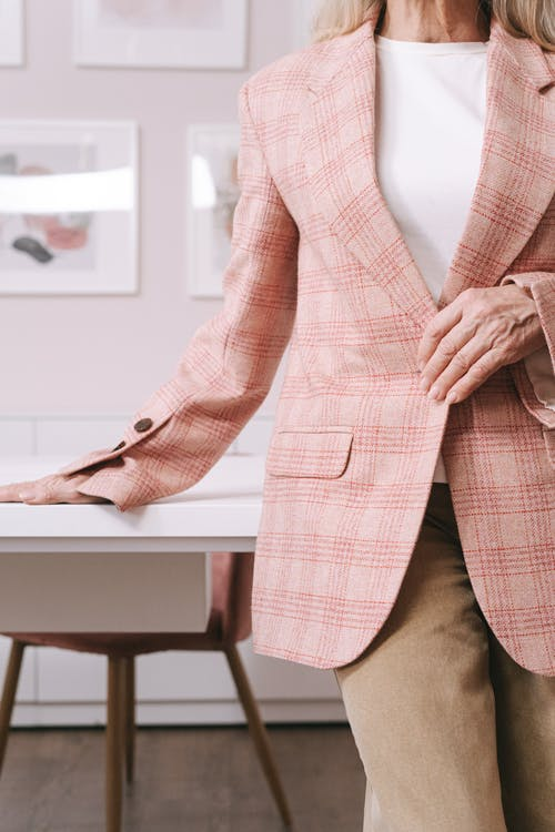 Woman in Pink and White Plaid Blazer Sitting on Brown Wooden Chair