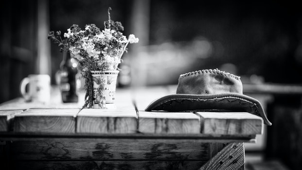 Grayscale Photography of Hat on Wooden Table