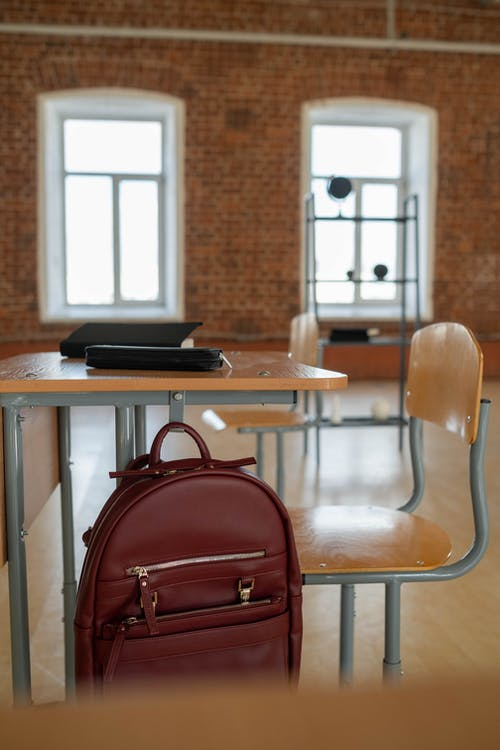 Leather Bag Hanging on Brown Wooden Table