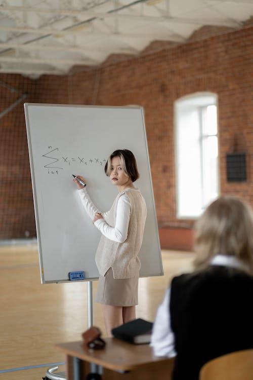 Woman in White Long Sleeve Shirt Holding White Printer Paper