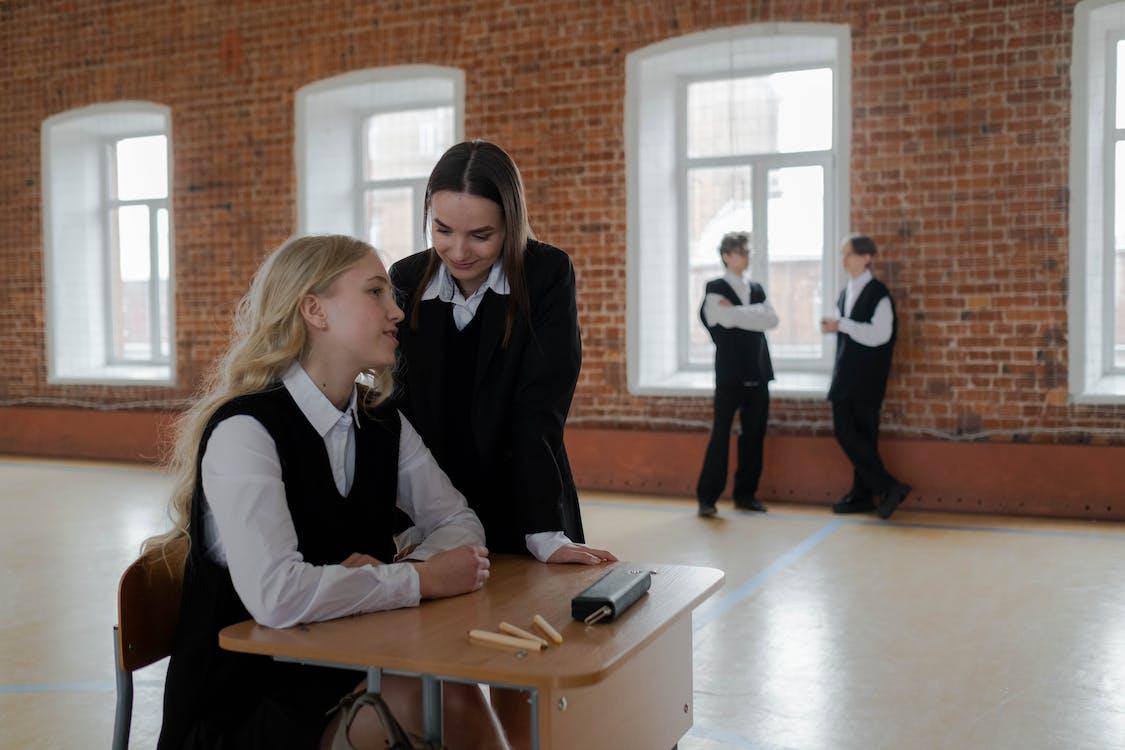 Woman in Black Blazer Sitting Beside Woman in Black Blazer