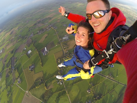 Woman and Man Wearing Overalls Sky Diving