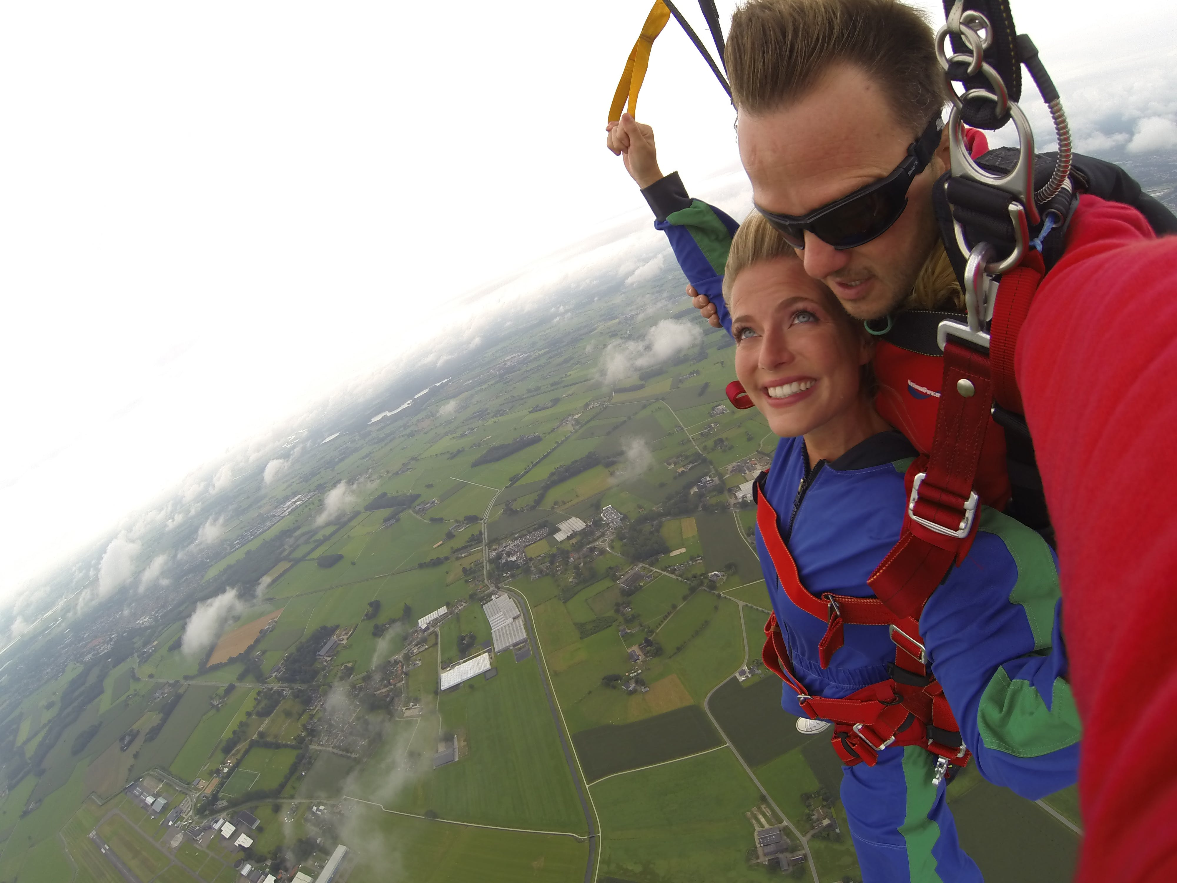 Couple Wears Red and Blue Long-sleeved Overalls and Body Harness With Parachute on Mid-air