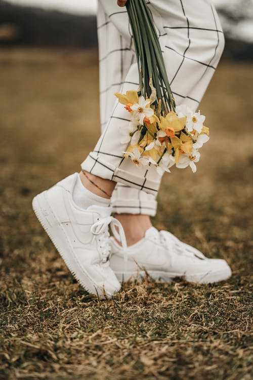 Side view of crop anonymous female in checkered pants and trendy footwear standing on lawn with blossoming daffodils in daytime