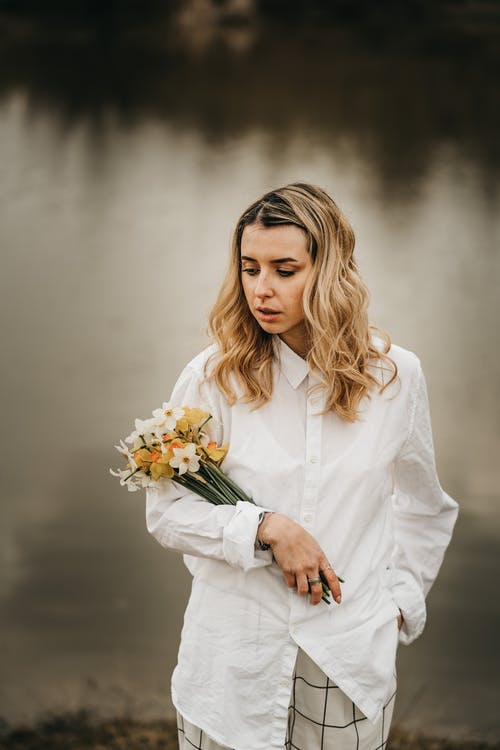 Stylish woman with blooming daffodils against river