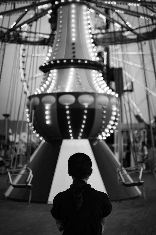 Black and white back view of unrecognizable person standing near merry go round in amusement park