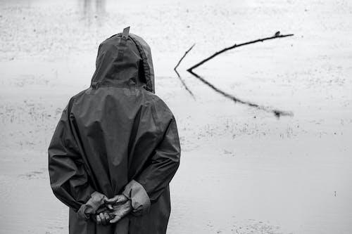 Anonymous fisherman in raincoat standing near lake in nature