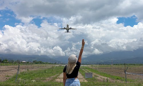 Unrecognizable woman standing in field under flying airplane