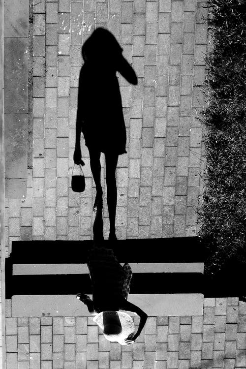 Anonymous woman walking on street in summer