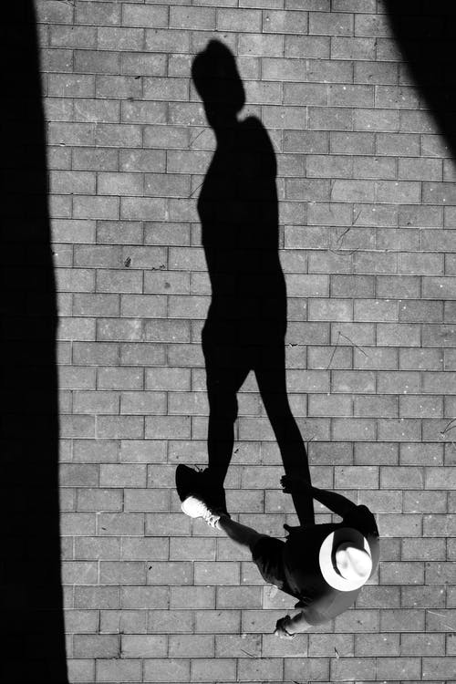 Black and white top view of faceless male in hat walking on paved street and casting shadow on sunny day in summer