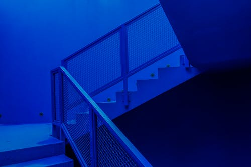 Staircase with metal railing in contemporary building designed in minimal style and illuminated by blue neon light