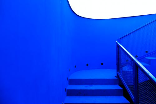 Stairway with metal railings inside contemporary building in minimal style with blue neon illumination