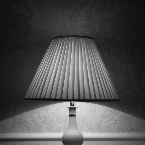 Black and white glowing lamp placed near wall and illuminating room designed in retro style