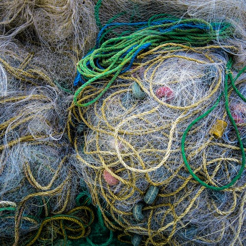 Top view of full frame background of pile assorted fishing nets and colorful ropes