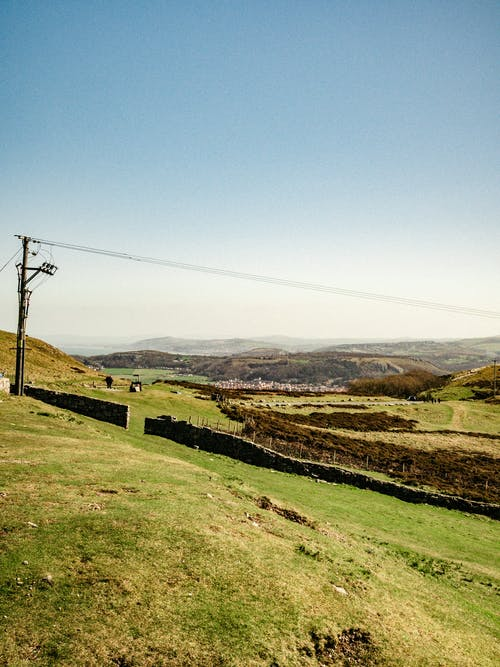 Picturesque scenery of utility line in verdant grassy hilly terrain under blue sky